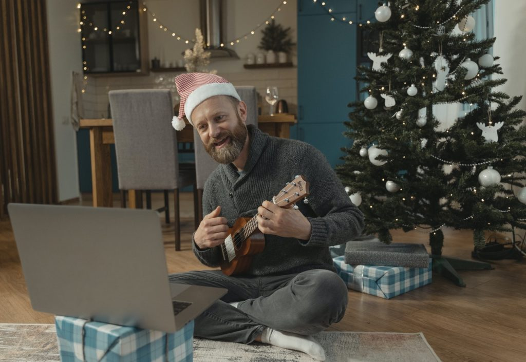 Man playing the guitar with a Christmas hat